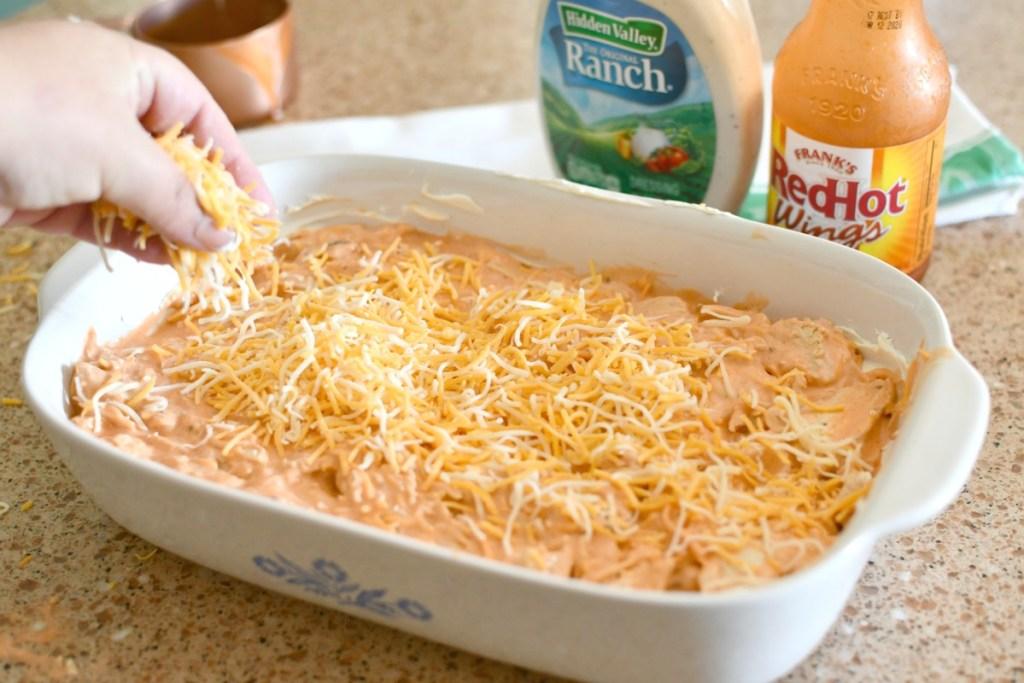 adding cheese to buffalo chicken dip