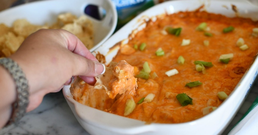 dipping chip into Frank's buffalo chicken dip