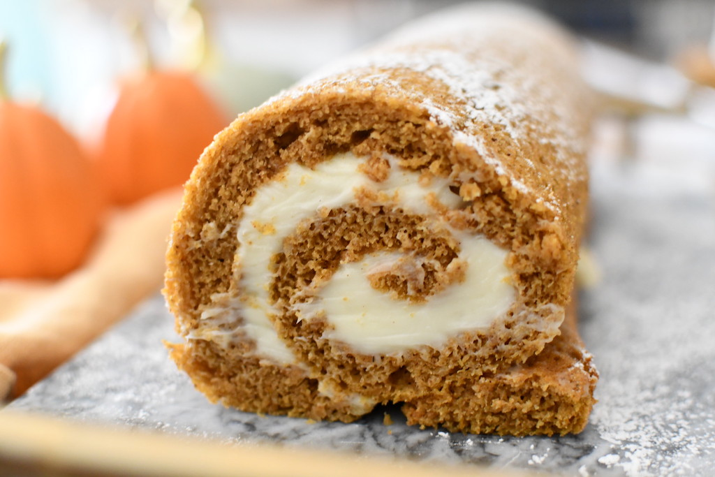 close up of pumpkin roll with cream cheese frosting
