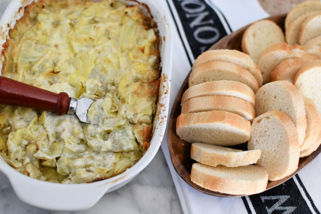 melted cheese artichoke dip in a casserole dish
