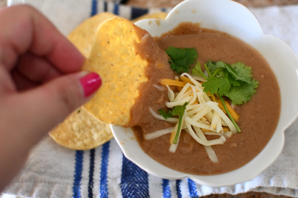 dipping tortilla chip in refried beans