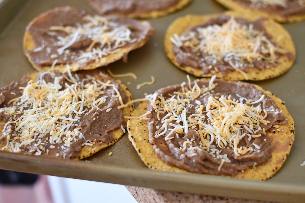 refried beans on tostitos with shredded cheese