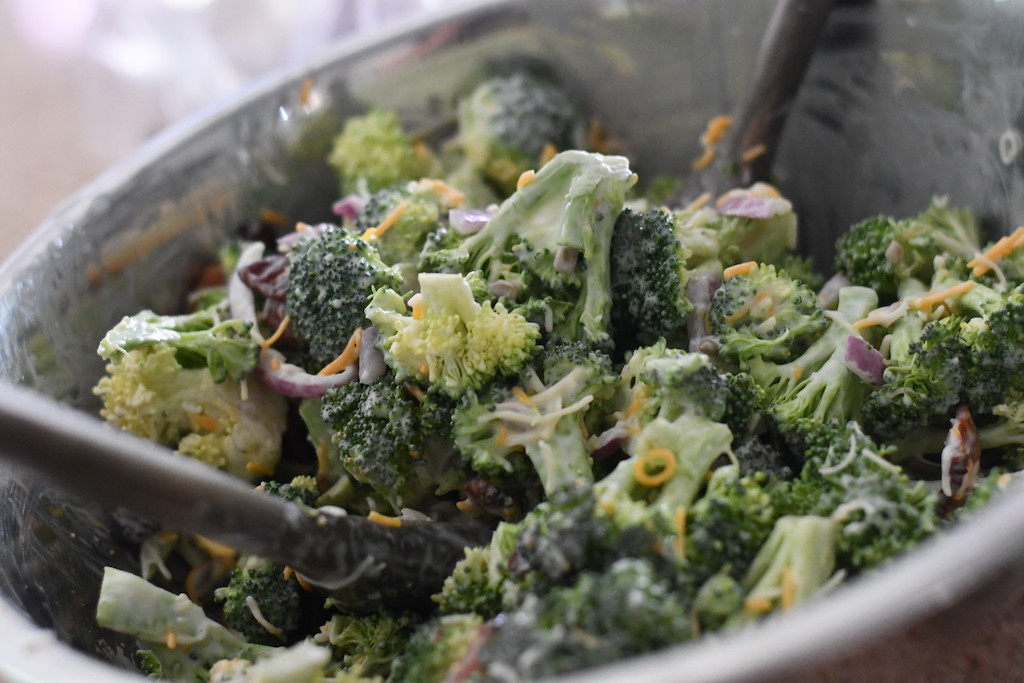 mix broccoli bacon salad in metal bowl