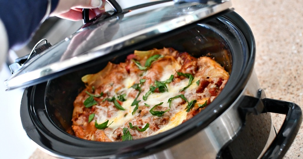opening a slow cooker with lasagna in it