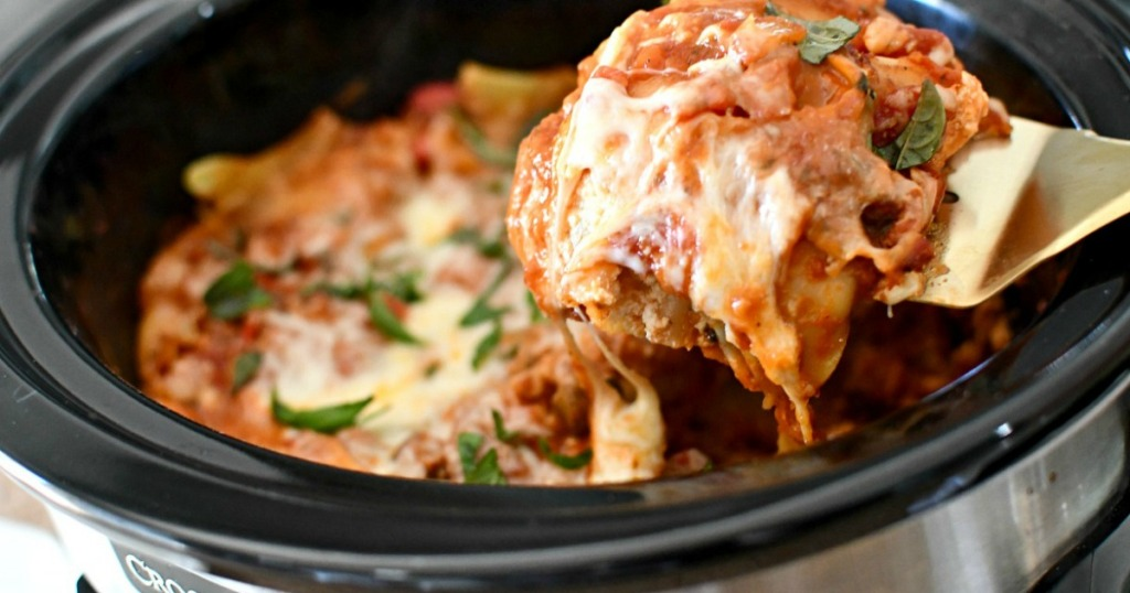 person dishing up lasagna from the slow cooker