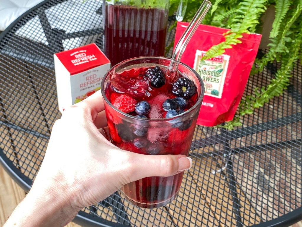 hand holding red drink with berries