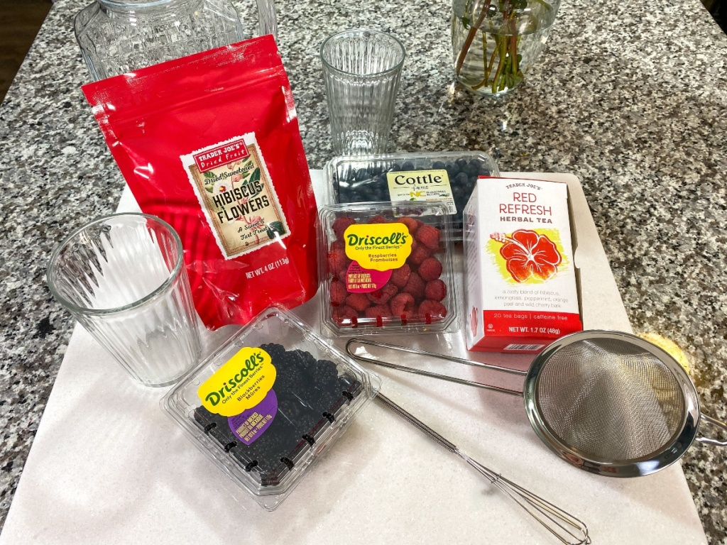 ingredients for a berry tea drink on kitchen counter
