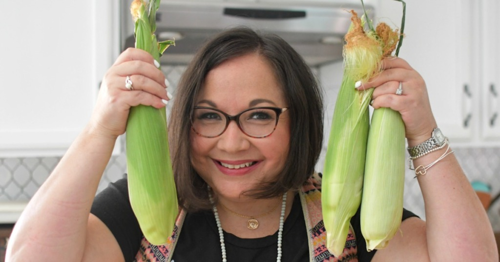 woman holding fresh corn on the cob