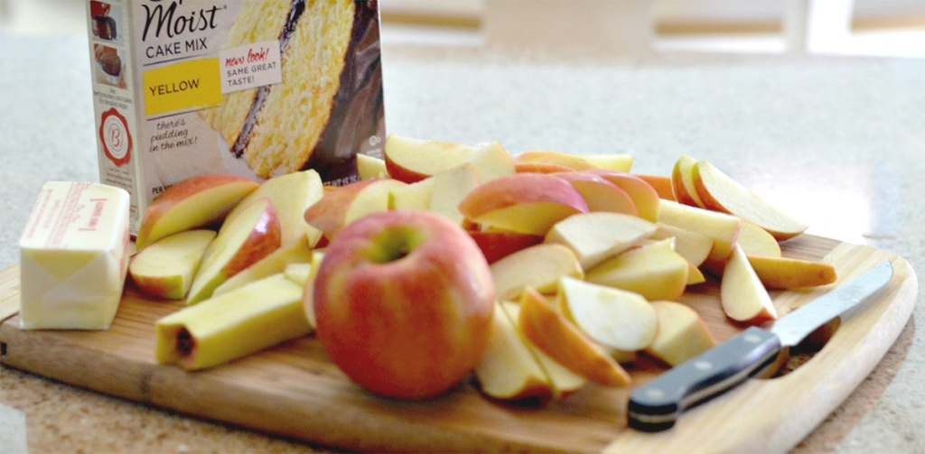chopped apples on cutting board next to cake mix