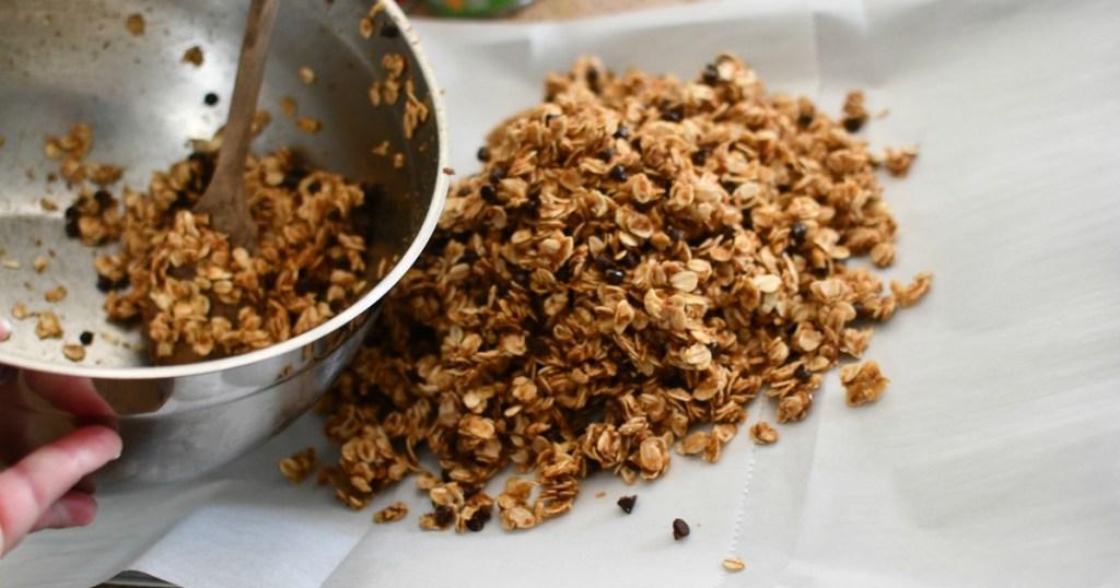 pouring granola bars onto a sheet pan