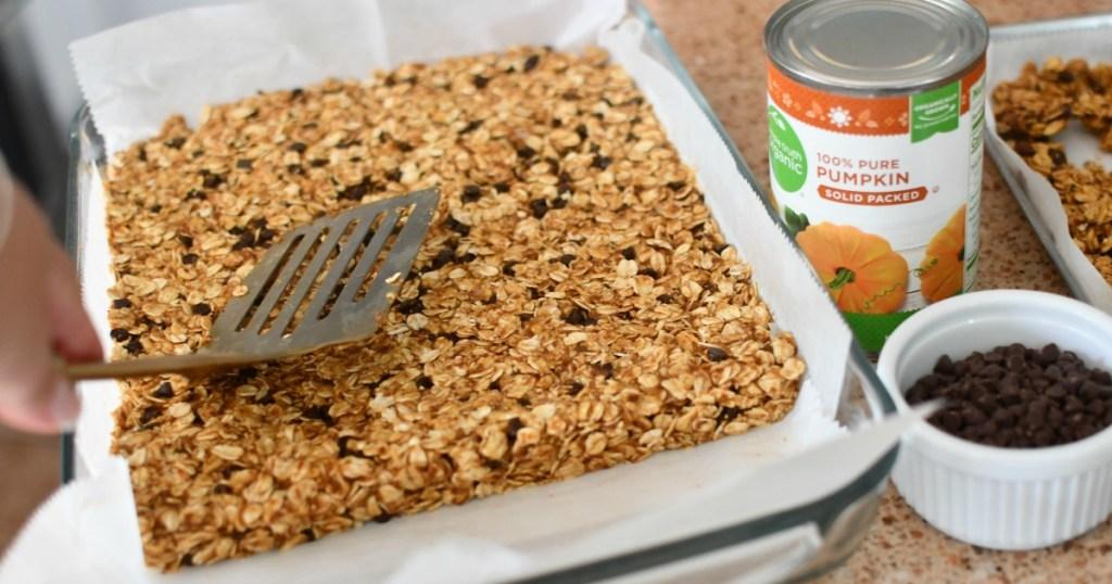 pressing granola bars into a pan