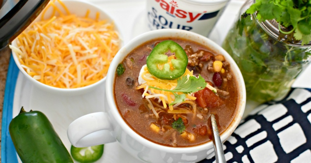 bowl of ranch taco soup next to cilantro and cheese