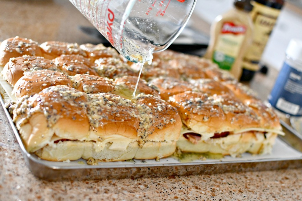 pouring butter mixture over party sliders
