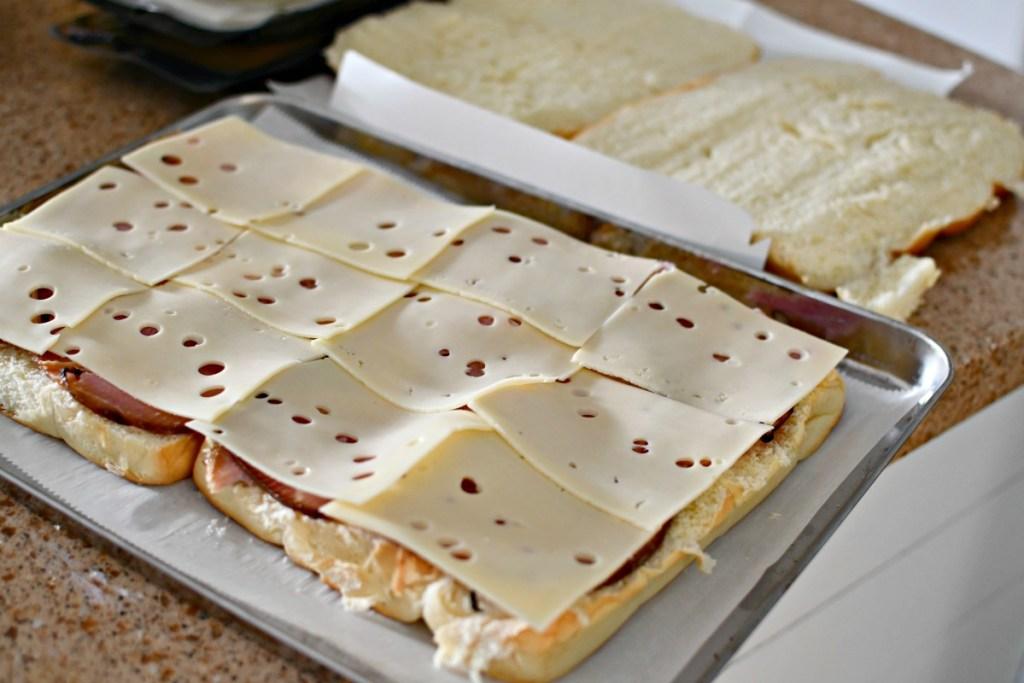 putting ham and cheese between hawaiian rolls
