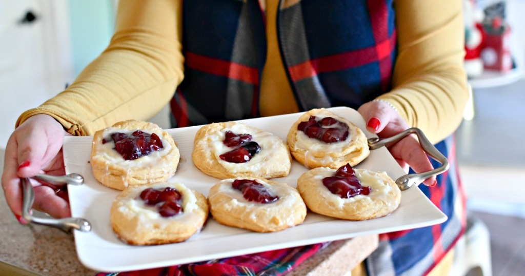 holding a tray of cream cheese cherry danish