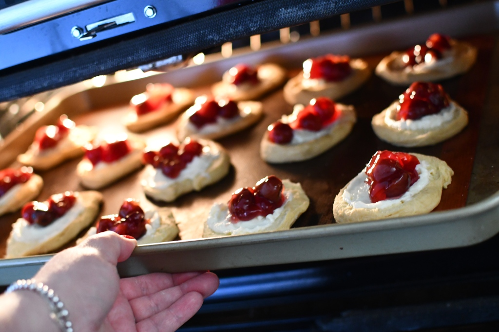 placing cherry cheese danish in the oven
