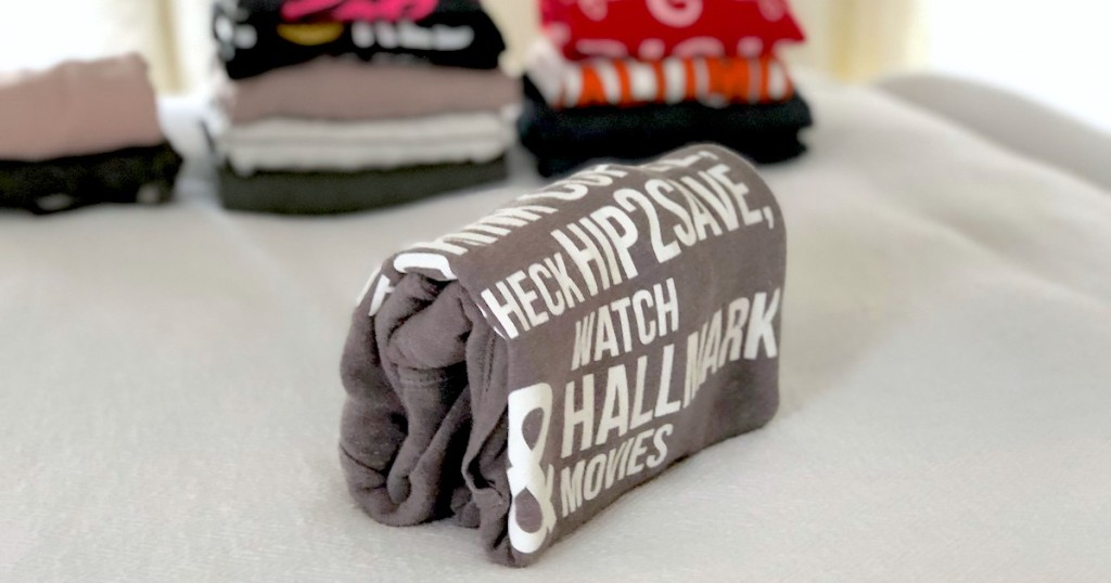 folded sweatshirt with words and laundry in the background