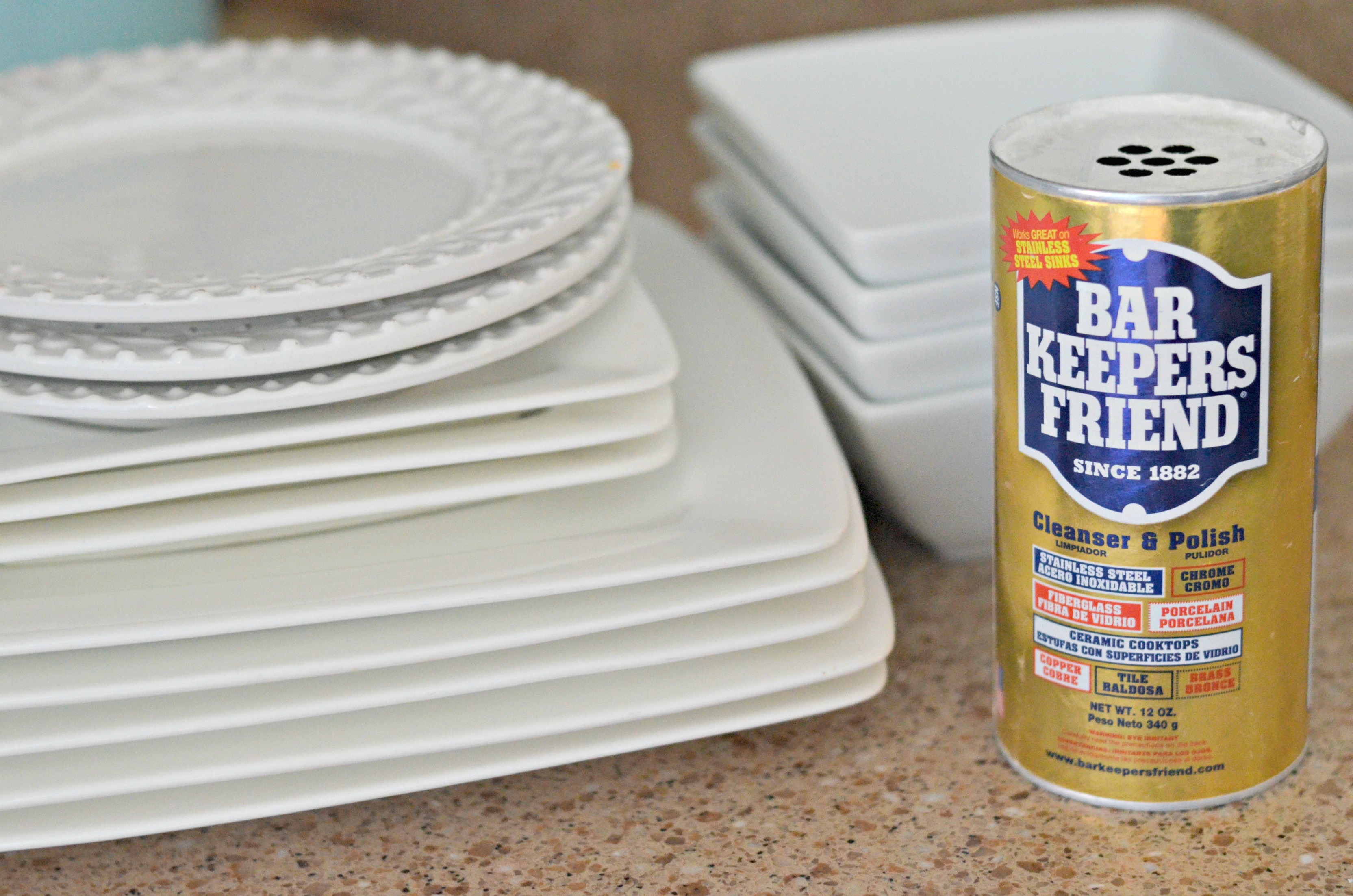 Bar Keepers Friend next to a stack of dishes