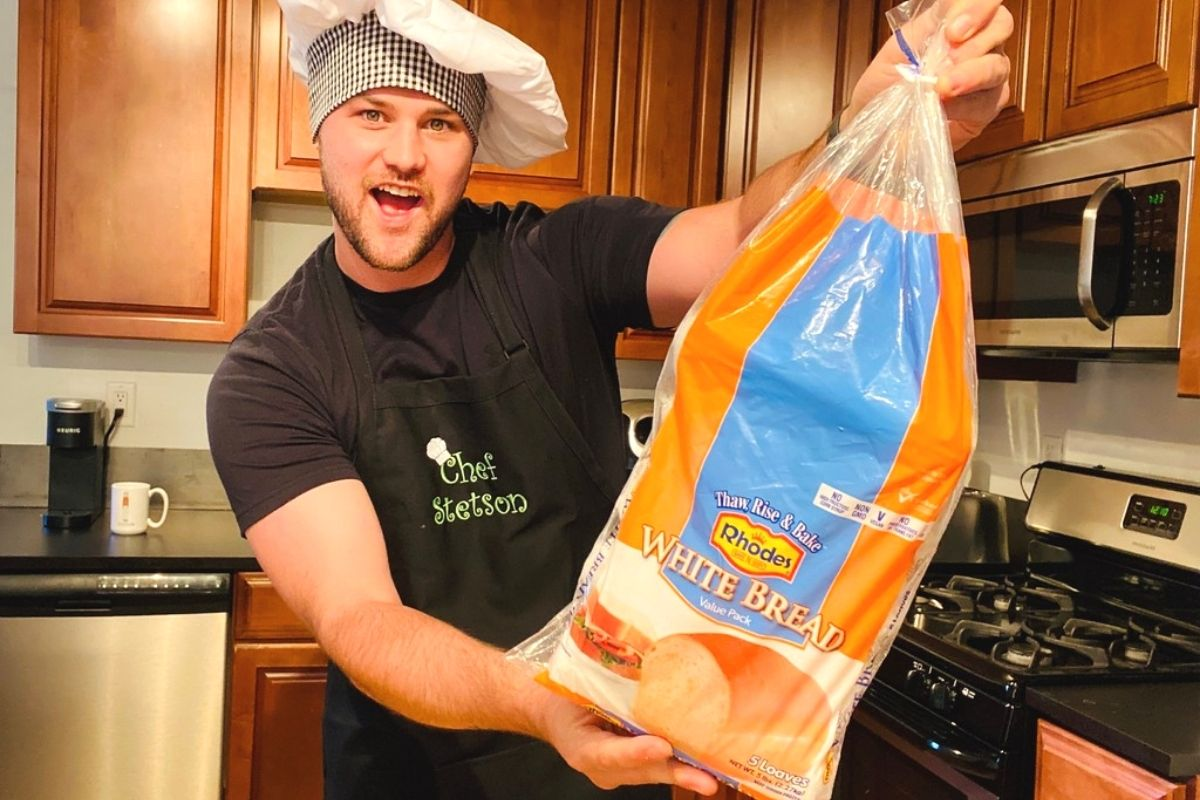 A man wearing a chef hat holding a loaf of frozen bread dough in a bag