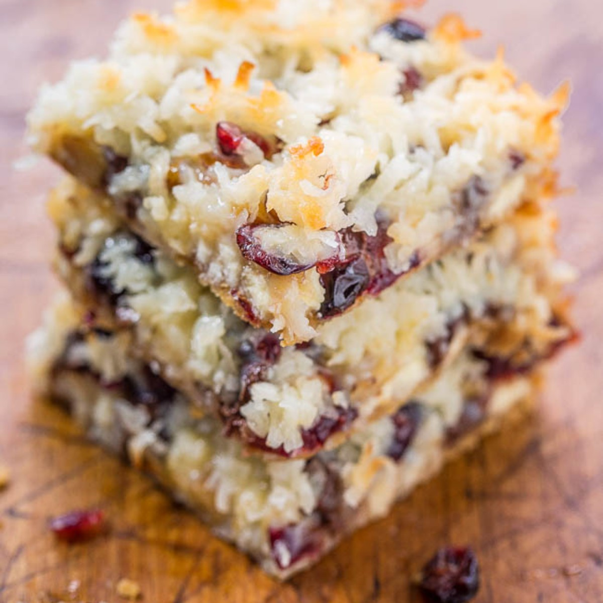 3 cranberry cookie bars stacked on cutting board
