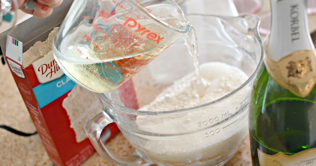 pouring champagne in cake mix to make cupcakes