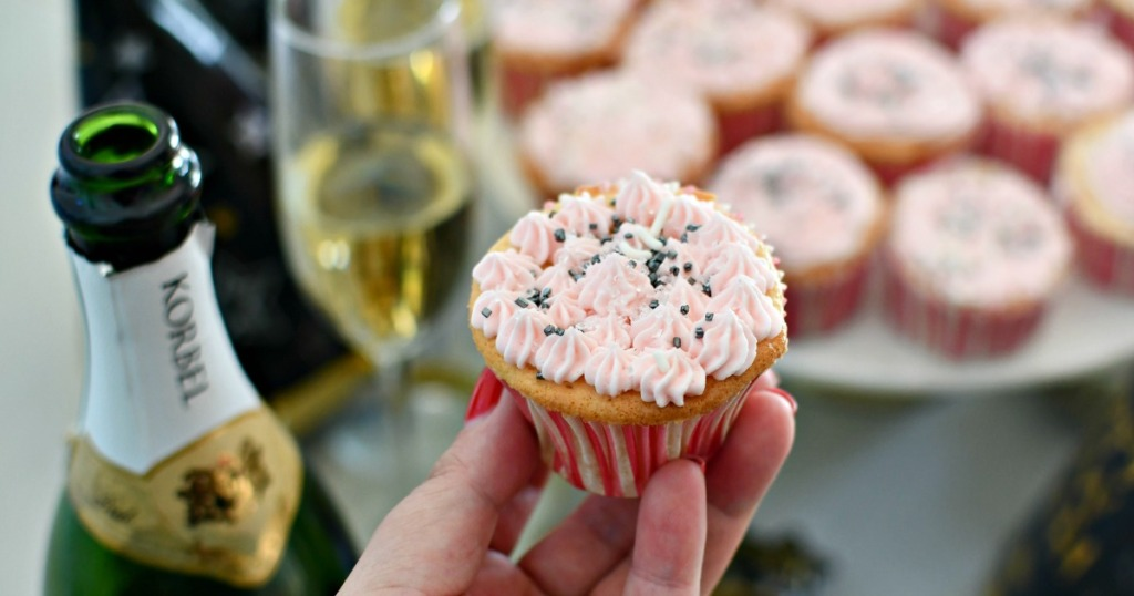 woman holding a pink champagne cupcake