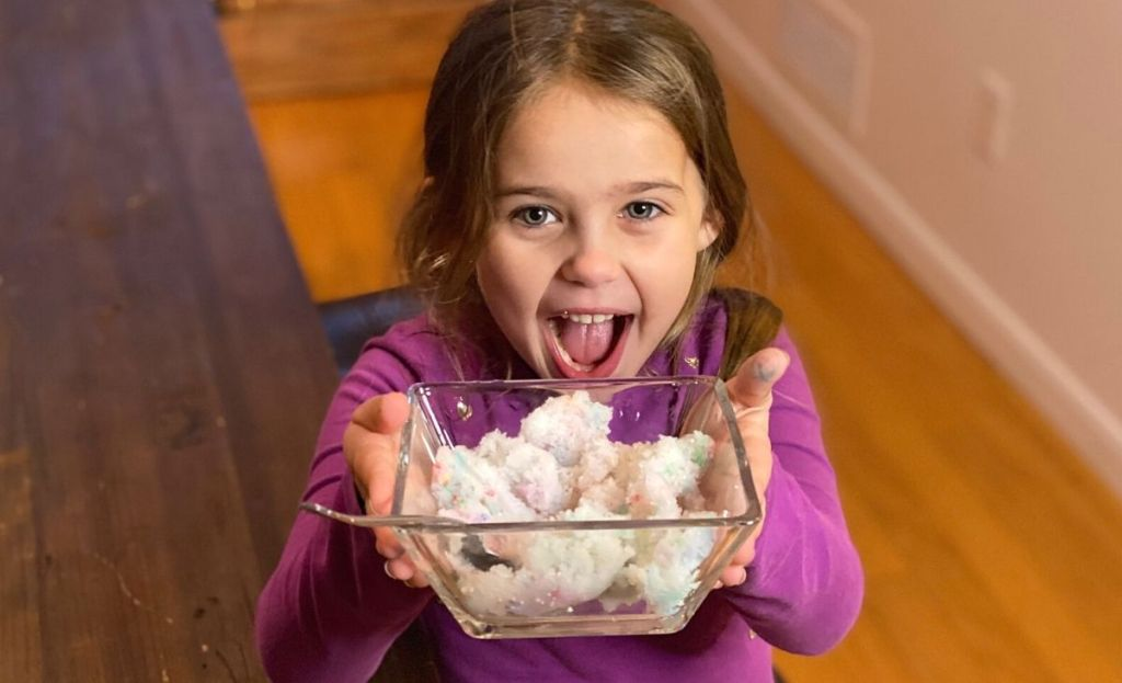 A little girl holding a bowl of snow ice cream