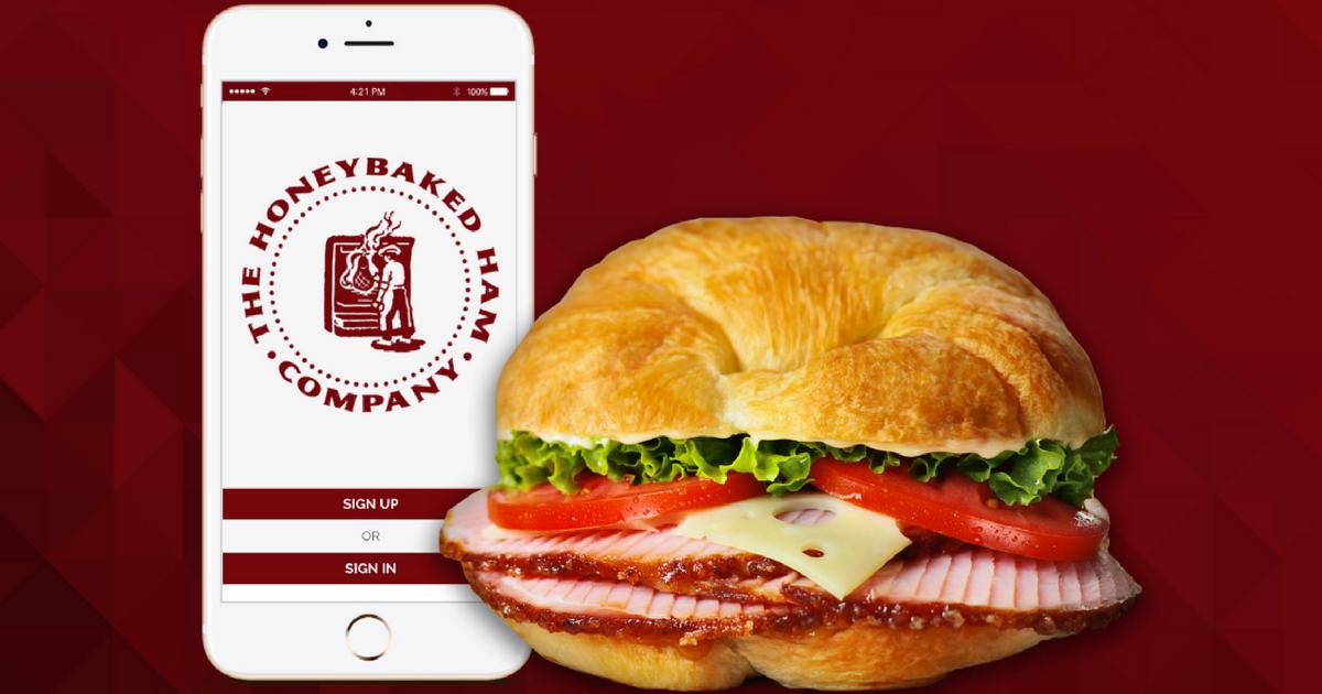 honeybaked ham app showing on smart phone next to sandwich