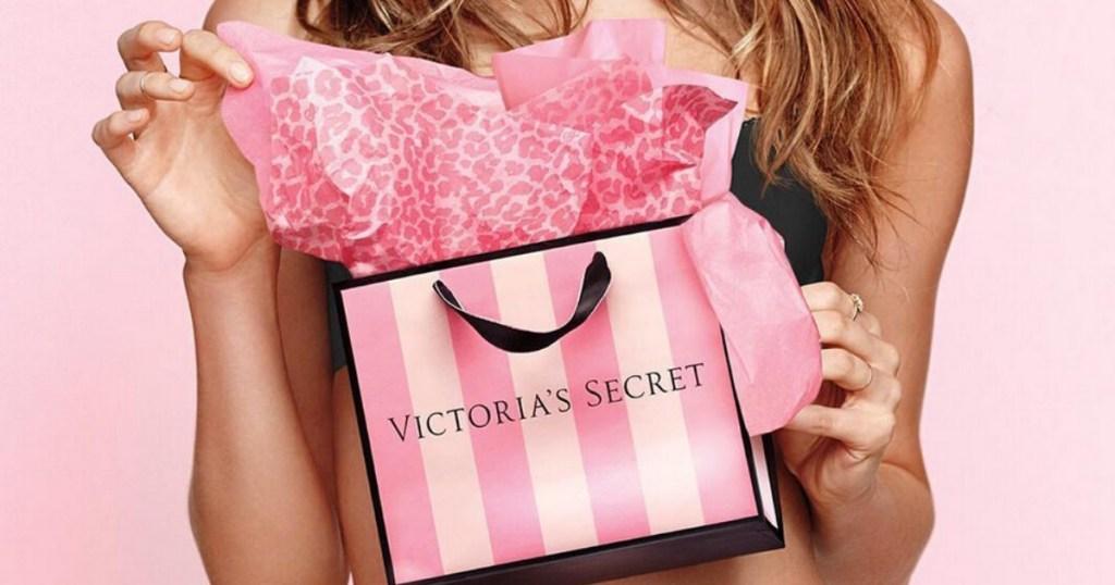 holding Victoria's Secret pink-striped bag