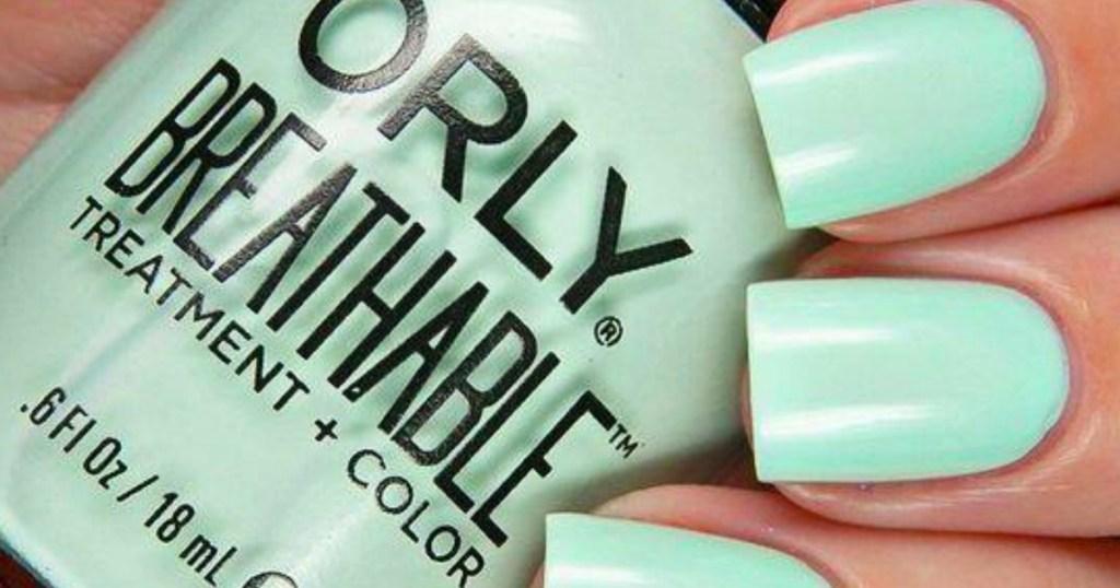 hand with green nails holding nail polish