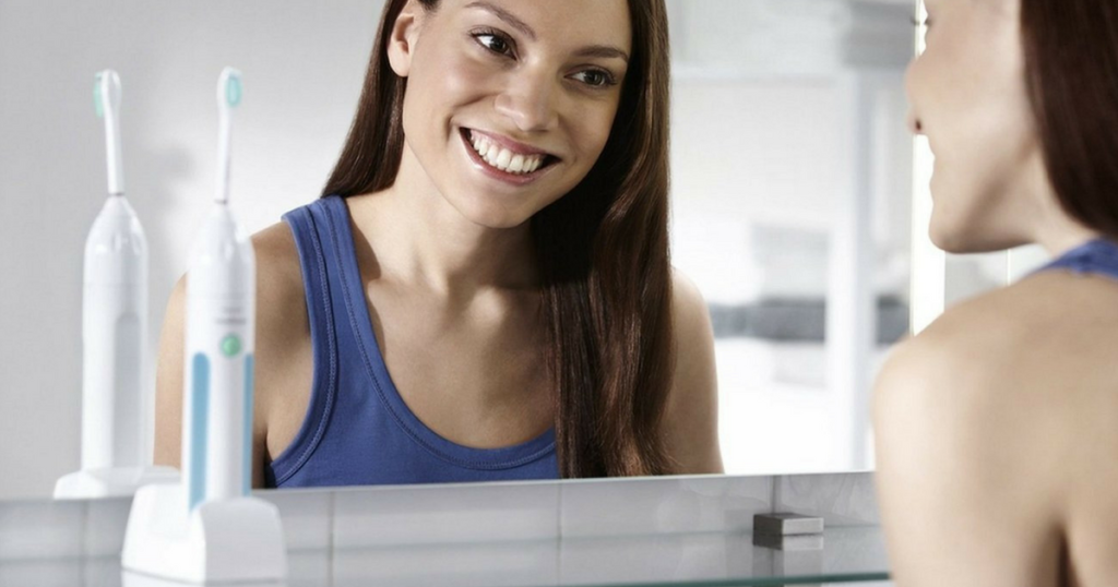 woman looking in mirror phillips sonicare toothbrushes