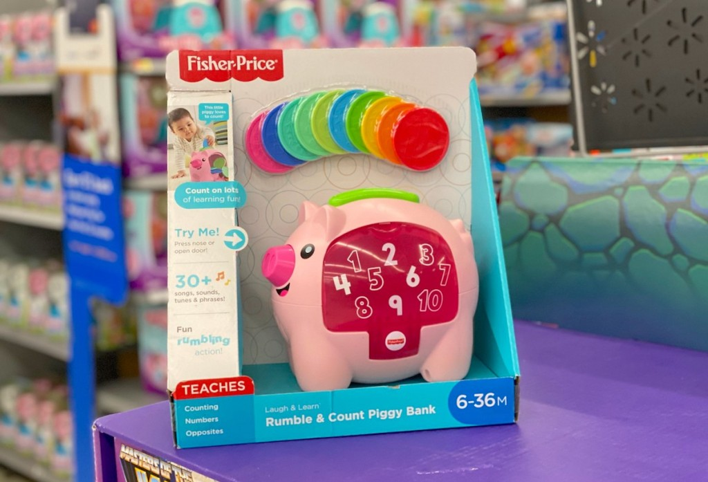 toy pink piggy bank sitting on purple shelf