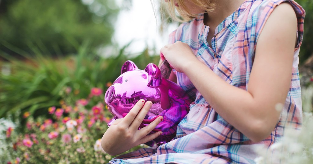 girl holding purple and pink shiny piggy bank outside