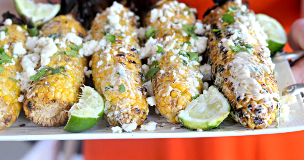 holding a tray of mexican grilled corn