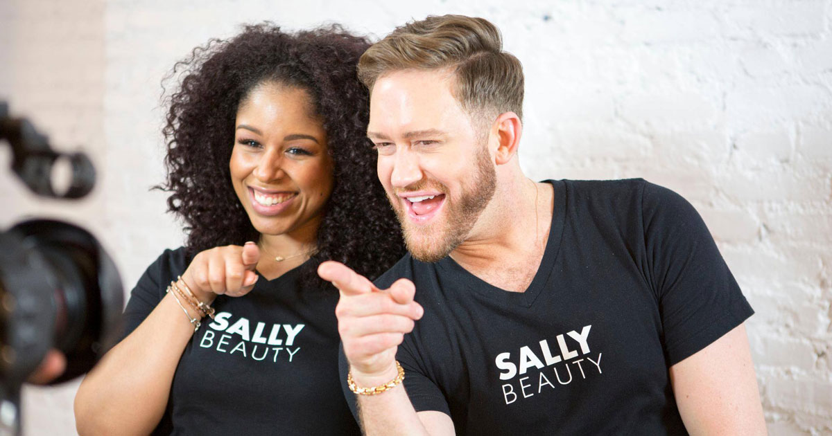 two people smiling wearing Sally Beauty Supply shirts