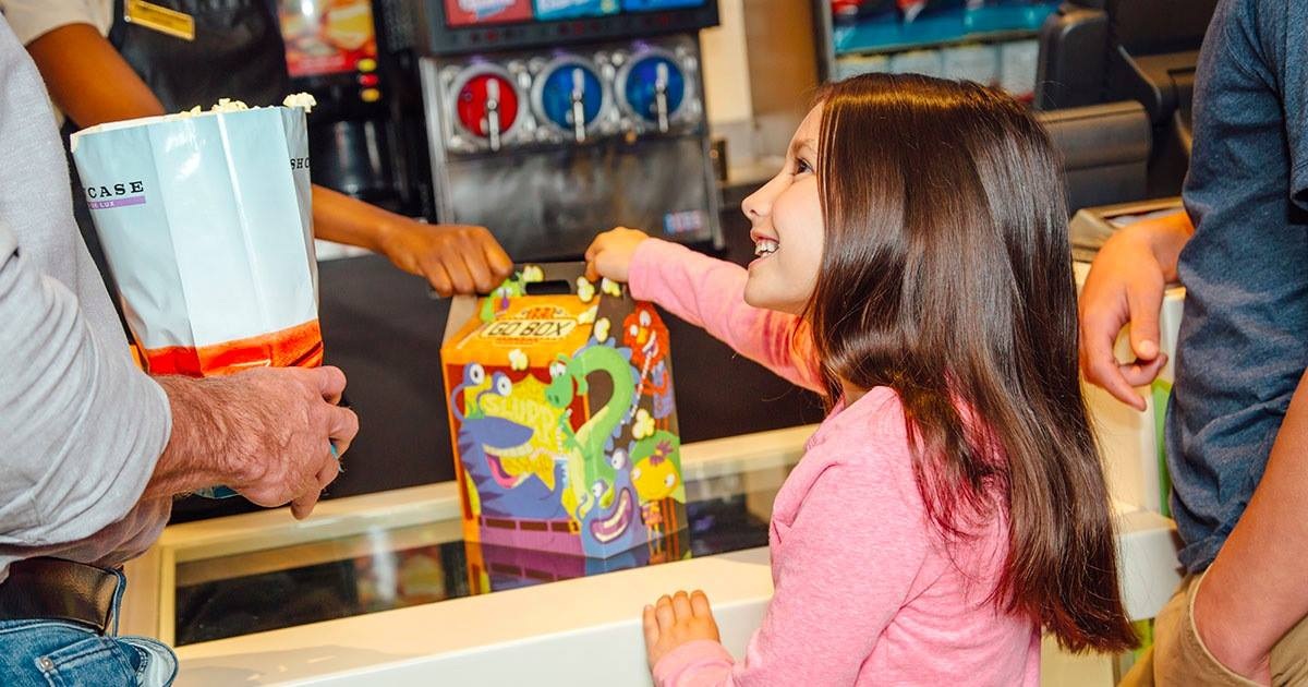 Showcase Cinemas - Young girl grabbing a snack box and smiling