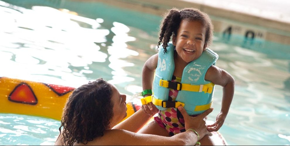 13 tips for your great wolf lodge vacation | giant slide and pool -- girl with life vest smiling