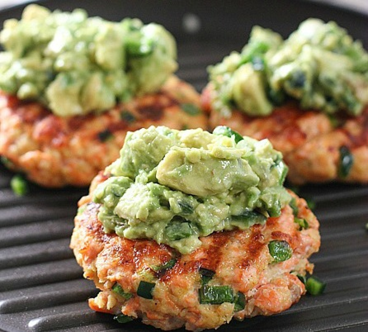 salmon burgers topped with avocado