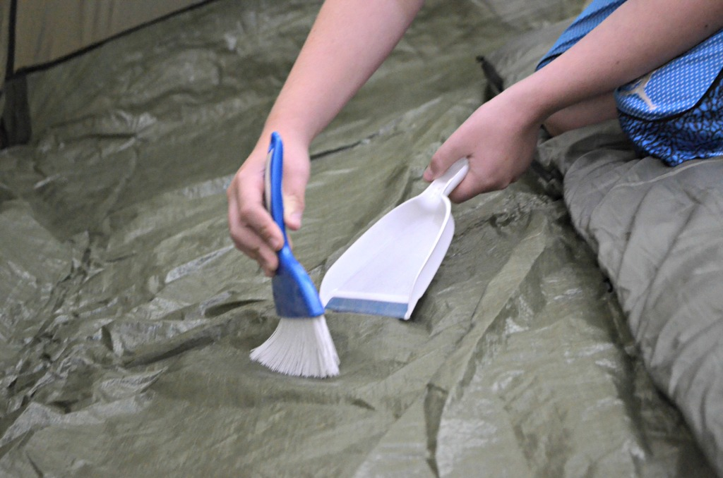 sweeping up dirt inside tent with dust bin