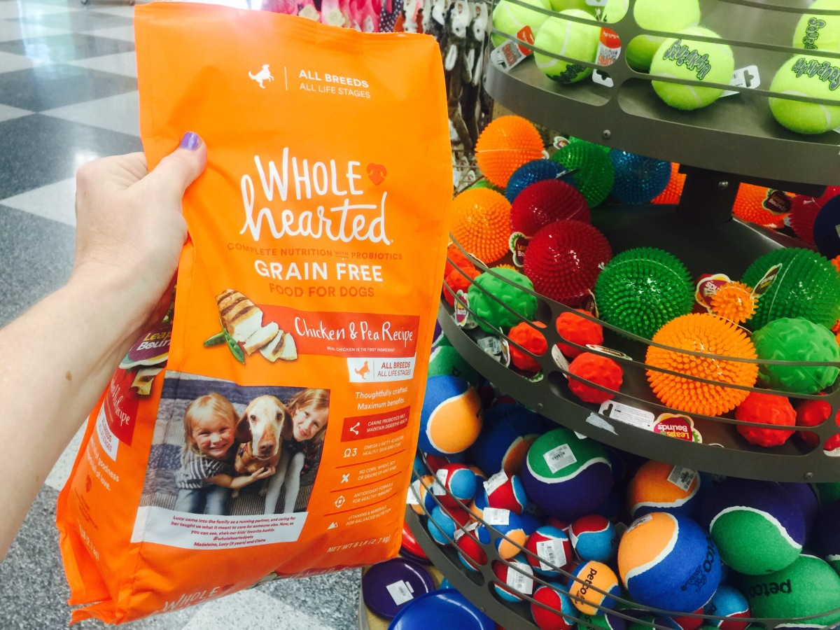 hand holding up a bag of whole hearted dog food in front of a display of dog toys