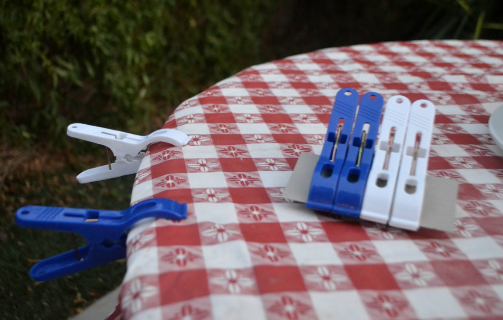camping hacks - using clamps on table to hold down tablecloth