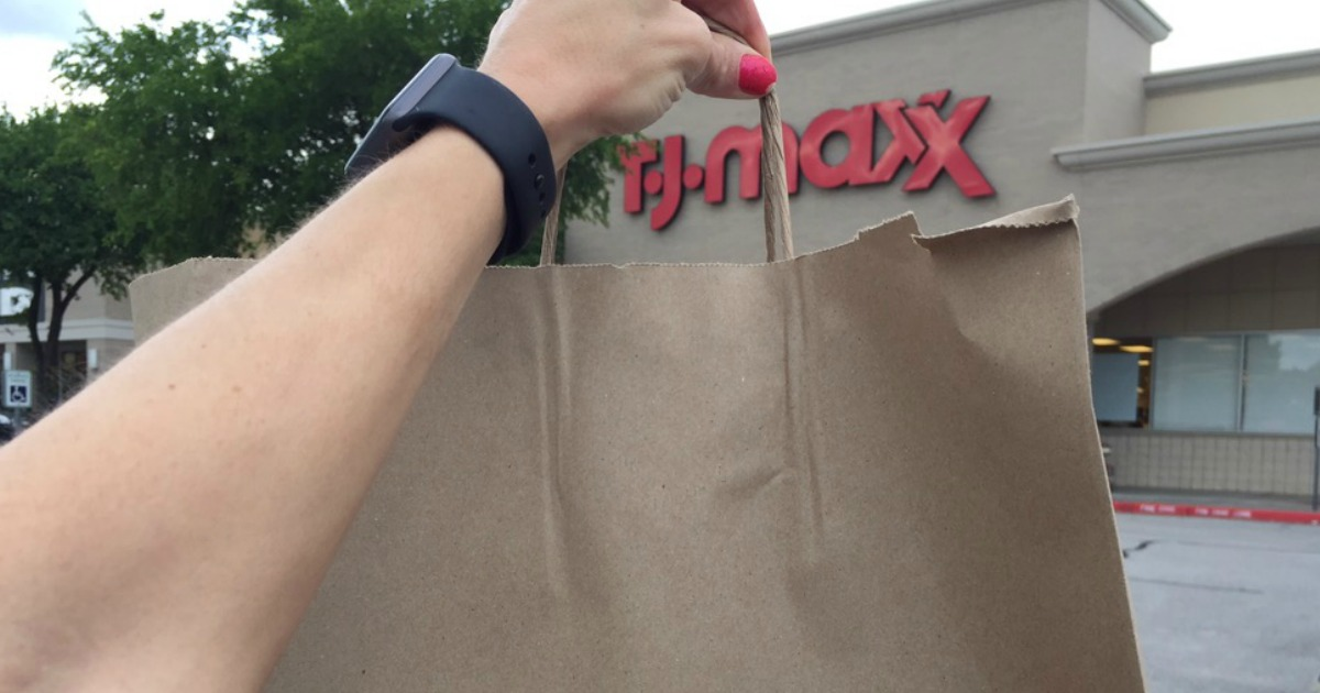 hand with brown paper shopping bag in front of T.J. Maxx store front in an outdoor shopping center