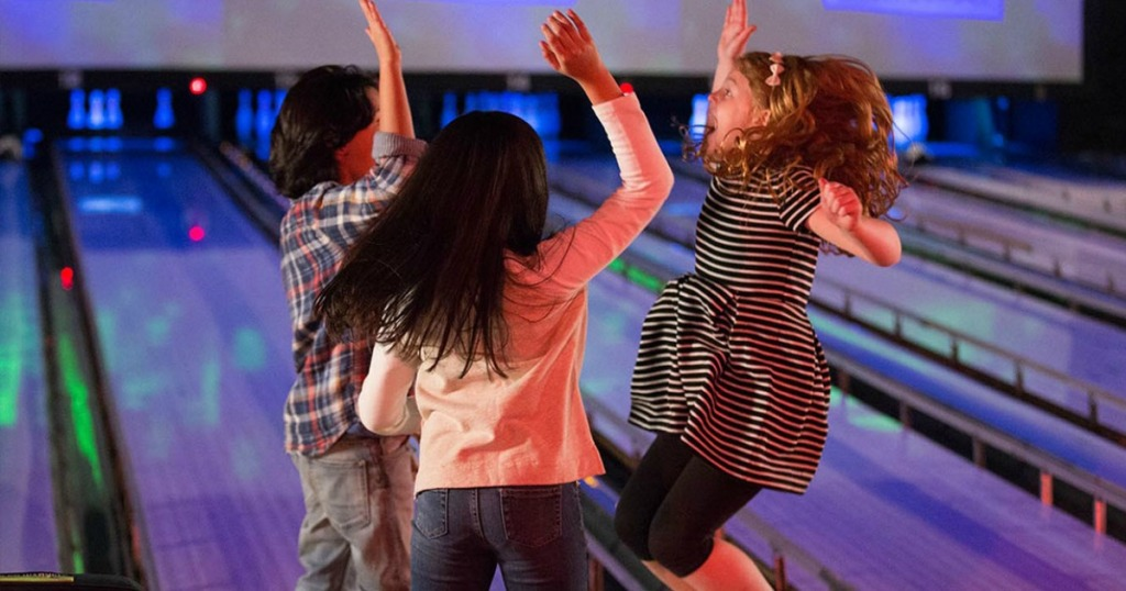 three kids high-fiving at bowling alley