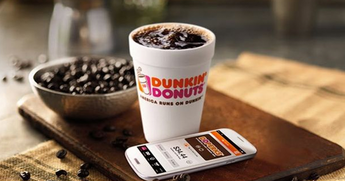 dunkin donuts coffee sitting on a wooden board next to a phone