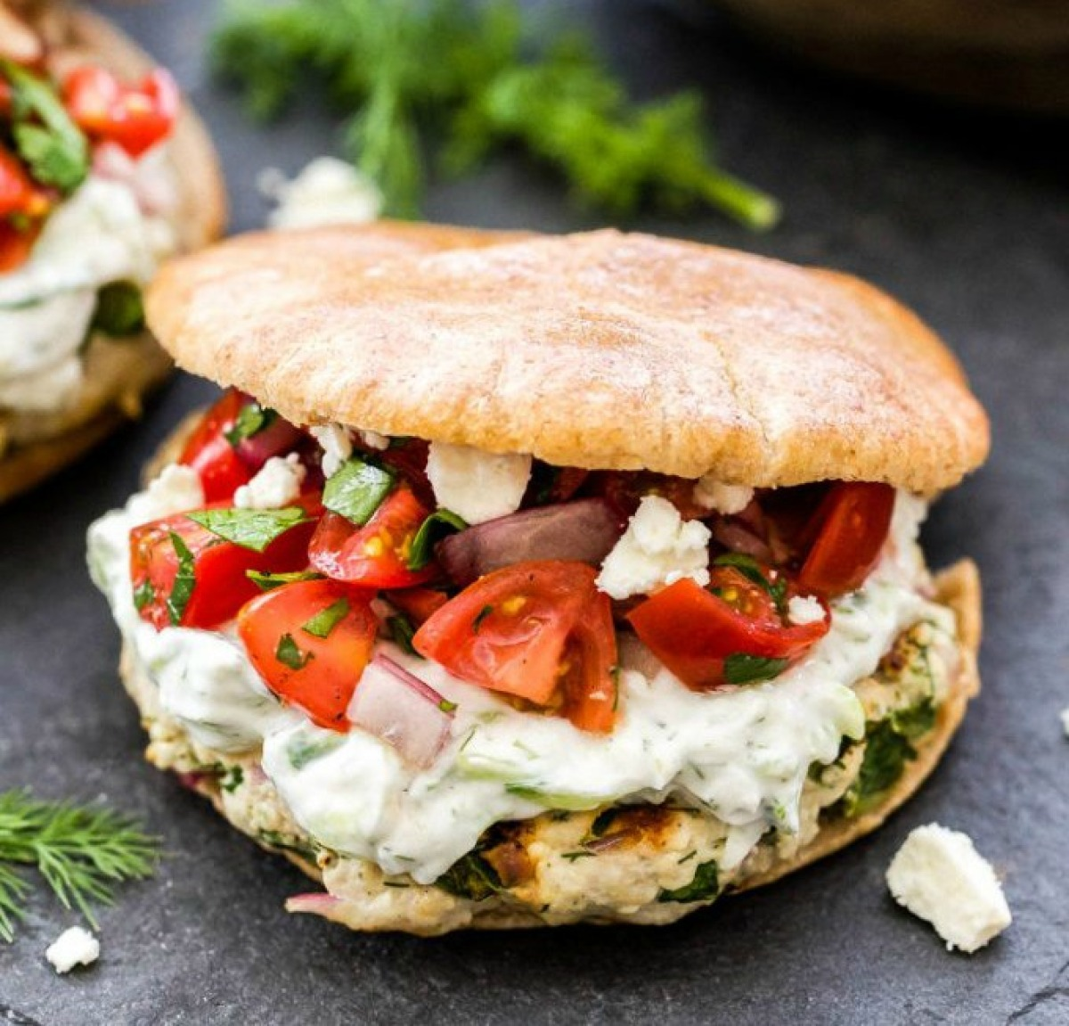 turkey burger with vegetables and white sauce on pita bread