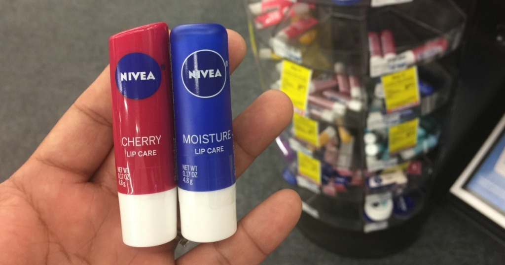 hand holding two tubes of lip gloss