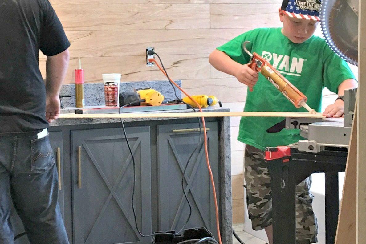 young boy applying caulk to wood panel