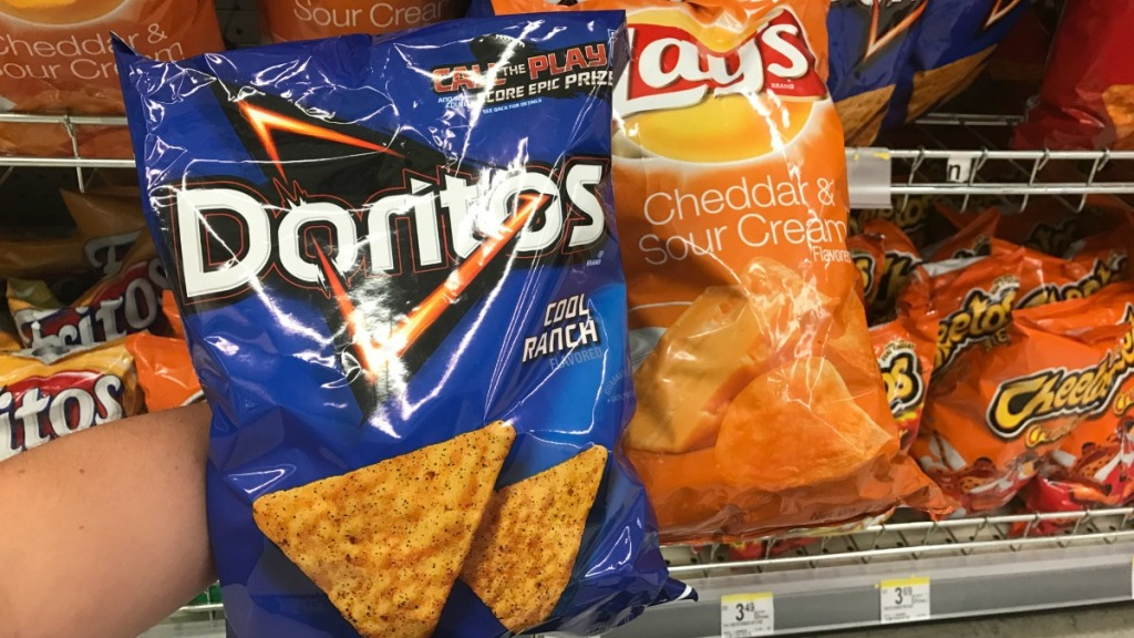 hand holding chips in front of shelf