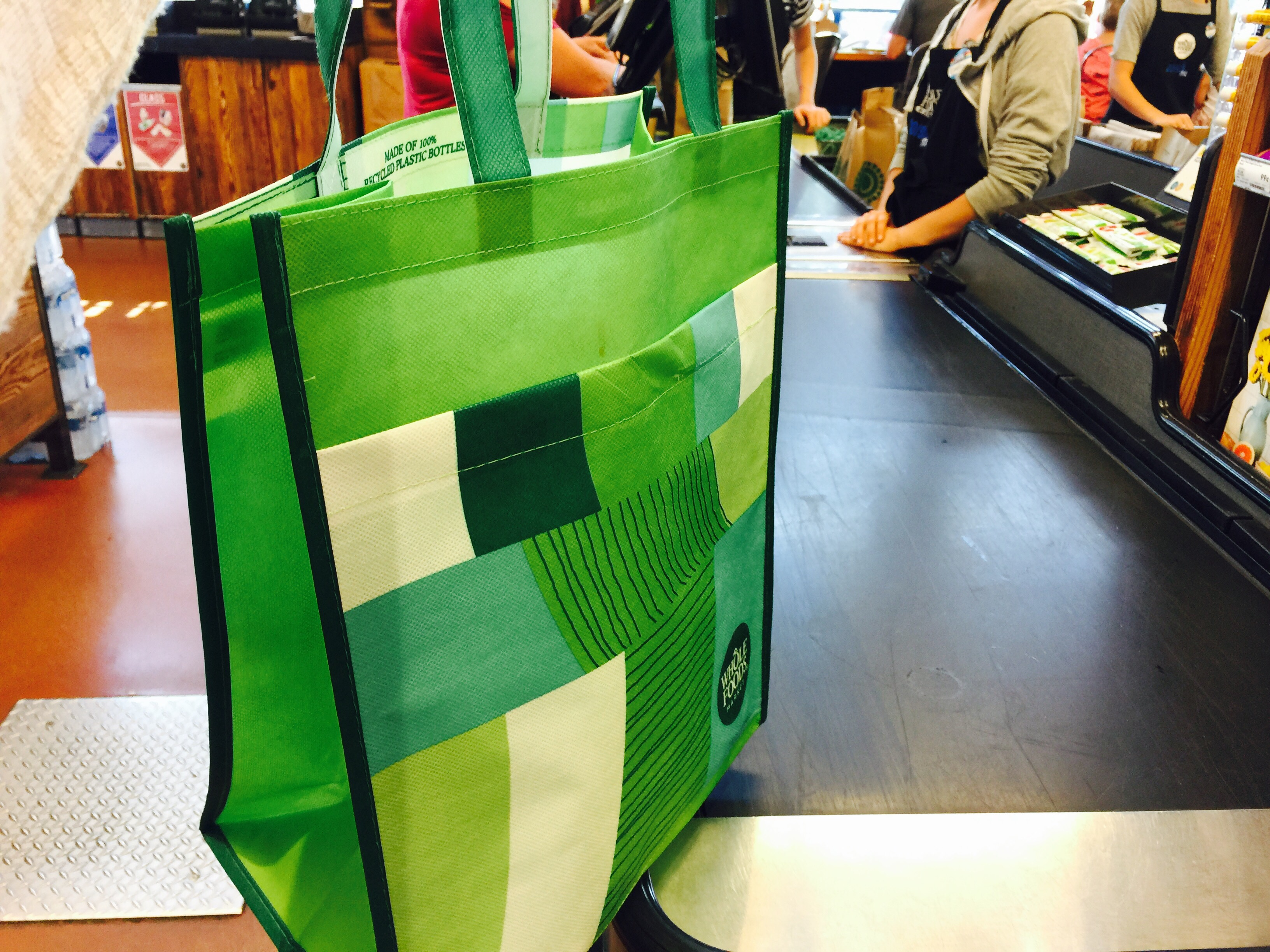money-saving hacks at Whole Foods Market – reusable bag on a conveyor belt