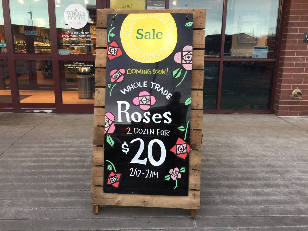17 practical ways to save at whole foods market – store sign on the sidewalk with a daily deal mentioned